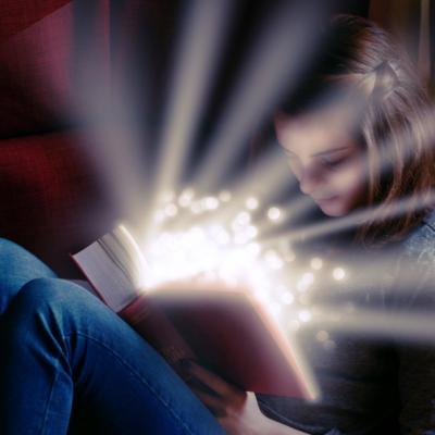 Una chica leyendo un libro que emana luz