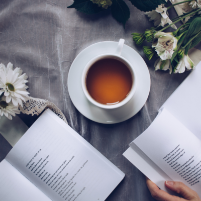 Café en taza con flores y libros de poemas alrededor