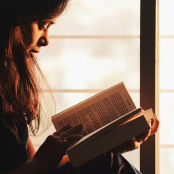 Una chica leyendo un libro a contraluz